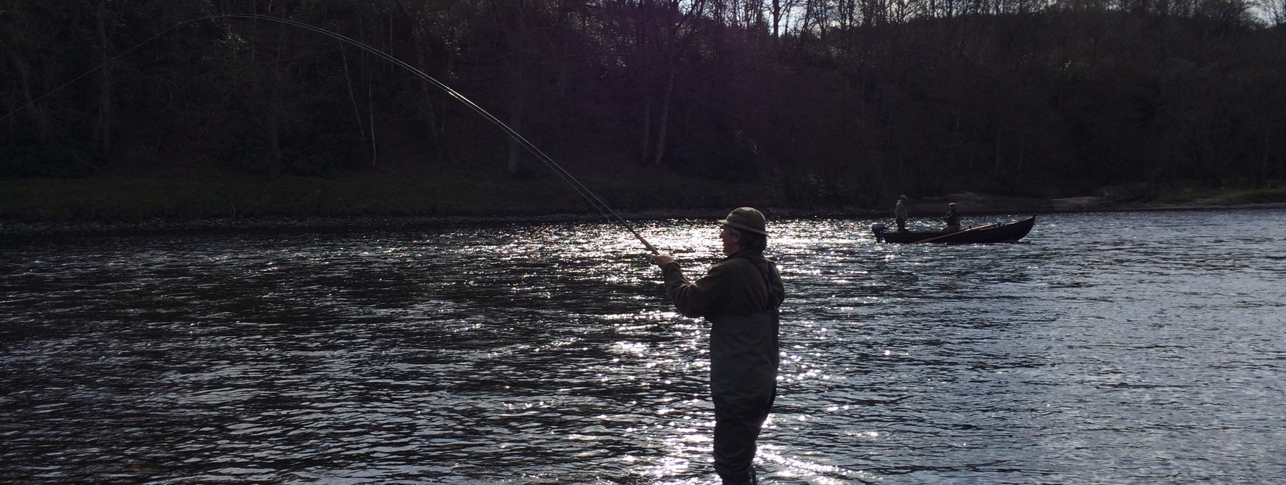 Playing a fish in The Burn - Playing a salmon on the River Tay on Murthly Beat 2 in the low spring sunshine (© Murthly Estate)