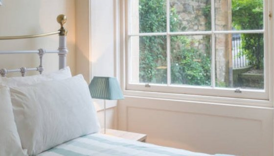 Business Accommodation - Bed in self-catering apartment with window looking onto garden