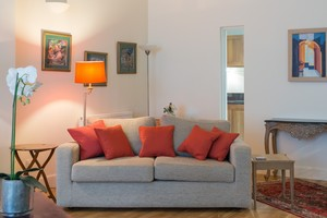 Grey sofa with red/orange cushions, standing lamp, artwork on walls.