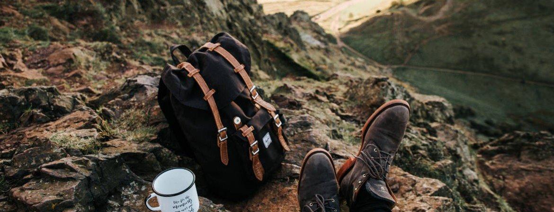 Walking boots, rucksack and mug on Arthurs Seat in Edinburgh