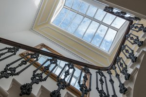 Grand staircase, looking up towards bright ceiling window.