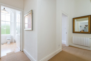 White hallway with mirrors leading to bathroom.