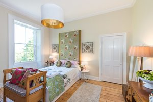 Bedroom with large patterned headboard, wooden floor and furniture