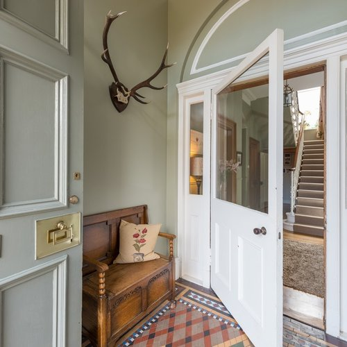 Entrance to house with antlers on wall, a wooden seat for two, and open white door leading to staircase.
