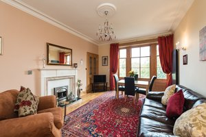 Large lounge with fireplace, tall windows, comfortable sofas, TV and dining area.