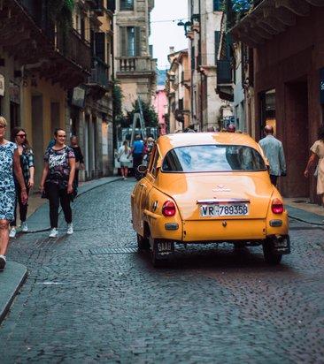 yellow-sedan-on-road-while-people-walking-on-sidewalk-1498843