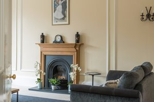 Traditional fireplace with clock and vases on mantelpiece.
