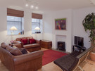 Open Plan Living Area - Warm and cosy with designer touches such as the Barcelona chairs! (© The Edinburgh Address)