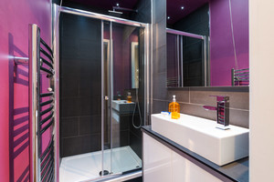 Shower room with dark tiles and bold purple walls.