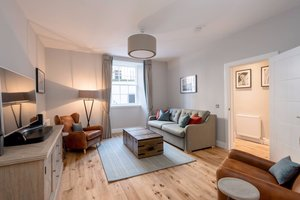 Spacious lounge with grey and brown colour scheme in Edinburgh West End apartment.