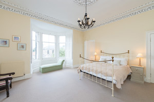 Large, light bedroom with bay windows, chaise lounge, kingsize bed, cornice cieiling,