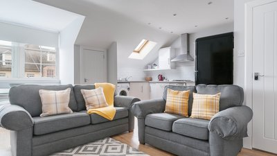 Edinburgh-Flats-holiday-rental-Royal-Mile-High-Street-lounge - Bright spacious Living/Dining/Kitchen open plan area with lovely wooden floors and 2 modern grey sofa and a double sofa bed which sleeps 2 people