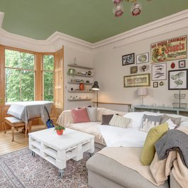 Family living room with large bay window providing green views in Edinburgh holiday let