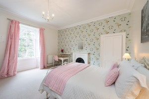 Bedroom with pink curtains, throw and cushions. Bird design wallpaper, fireplace and desk.