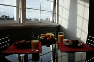 Table set for breakfast for two, with sunlight shining in from the window.