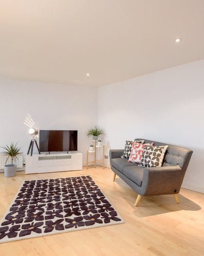 Sandport Way 3 - Spacious, contemporary open plan living room / dining area, featuring designer rug and cushions in an  Edinburgh holiday apartment.