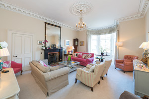 Spacious drawing room with bay windows, fireplace, large mirror, chandelier ...