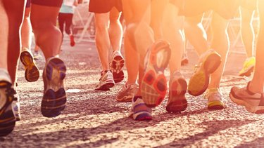Runners legs and feet running on tarmac