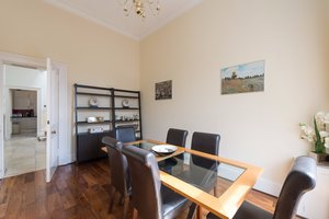 Coates Gardens Apartment Dining Room - Spacious dining room with wood and glass table and six dark leather chairs.