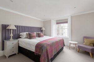 King Bedroom with pink and purple soft furnishings