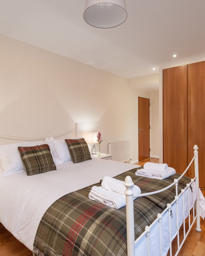 The Park (Holyrood Road) 3 - Double bedroom with tartan throw and cushions and large built-in wardrobe