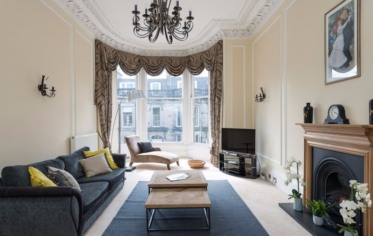Spectacular Drawing Room with large bay windows, chandelier and fireplace within Edinburgh holiday apartment.