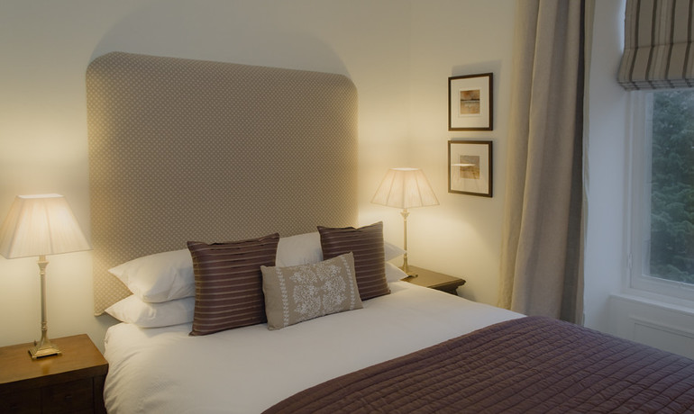 Master Bedroom - Decorated in warm tones and boasts a double bed with view of the garden. (© The Edinburgh Address)