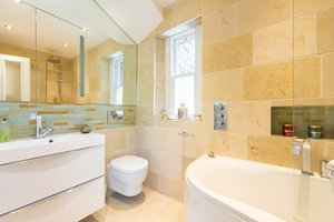 Bathroo with white bath and sink, beige tiles, large mirror