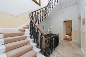 Grand staircase in light hallway, within Edinburgh holiday home.