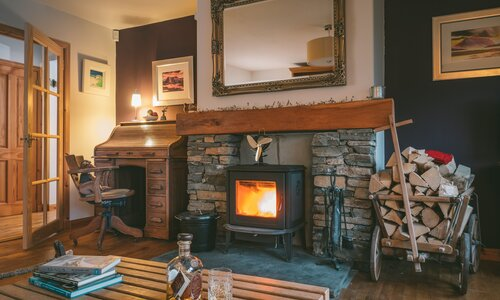 The Shambles - Luxury Lodge in Aviemore with hot tub and BBQ hut - Cosy living room with wood burning stove and antique furniture at The Shambles, Aviemore