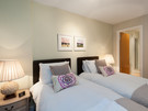 Parkgate (Holyrood Road) 6 - Twin room with zip'n'link beds and decorative cushions with purple flowers on