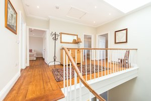 Open upstairs hall with classic wooden features.