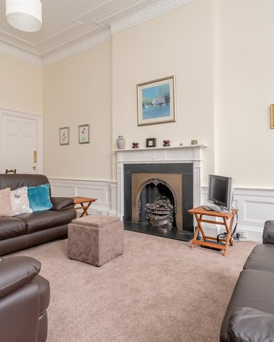 Edinburgh-Flats-self-catering-holiday-Melville-Street-Lounge - Lounge with fireplace, brown leather sofas and sofa bed which sleeps 2