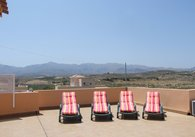 LG sunbeds on roof terrace with mountains