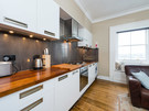West Newington Place Apartment Kitchen Area - Modern, white kitchen with wooden worktops.