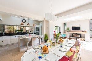 Modern dining area with colourful chairs and kitchen in background.