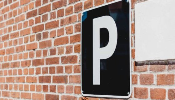 Parking - Parking sign on brick wall (© Photo by Georgia de Lotz on Unsplash)