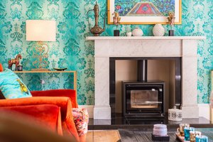 Bold teal wallpaper, white marbled fireplace and wood burning stove.