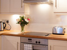 Drummond Street 7 - Fully fitted family kitchen with vase of flowers in Edinburgh holiday let