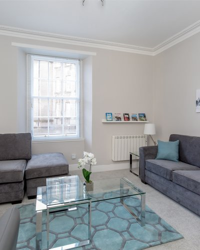 Edinburgh- - Light and spacious living room and dining area with grey sofas and a sofa bed for 2 people, dining table and chairs