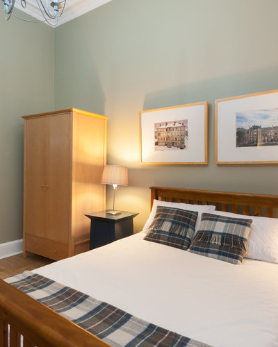 Haymarket Terrace 2 - Double bedroom with wooden bed frame and framed wall pictures