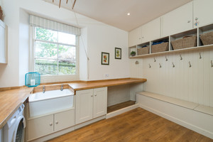 Large utility room with washing machine, sink, storage space ...
