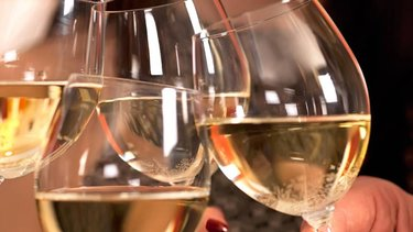 A toast with four glasses of white wine