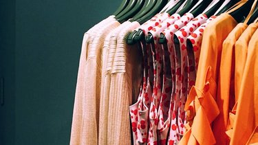 Colourful clothes hanging on a rail in a fashion boutique.