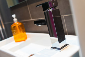 Close up of tap and toiletries on white sink.