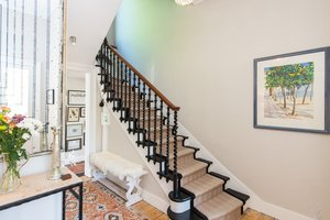 Staircase in hallway with black detailed bannister