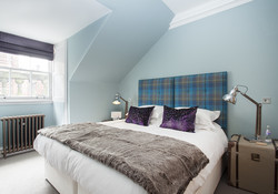The second bedroom is painted in a soothing duck egg blue with Scottish touches
