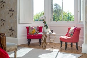 Pink chairs with colourful cushions under bright bay windows.