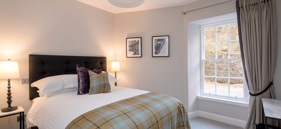 Master Bedroom with kingsize bed and tartan throw in Edinburgh West End Apartment.