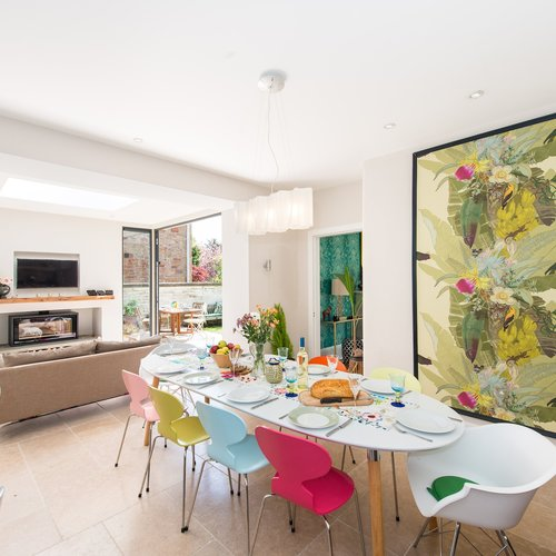 Modern dining area with colourful chairs and lounge in background.